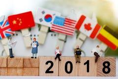 Miniaturleute: Geschäftsteamlesung auf hölzernem Block mit Nr. 2018 Stockbilder