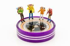 Miniaturleute: Gruppe Wanderer stehend auf Kompass mit als Hintergrundreise, Geschäftskonzept Lizenzfreie Stockfotos