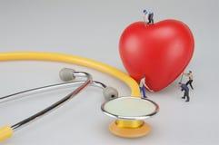 Miniaturleute interessieren sich das Herz und das Stethoskop lizenzfreie stockbilder