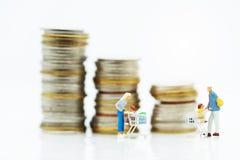 Miniaturleute: Käufer mit Einkaufskartenstellung vor Münzenstapel stockfotografie