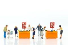 Miniaturleute: Käufer mit Rabatt für Einkaufseinzelteile unter Verwendung als Einkaufsgeschäftskonzept Lizenzfreie Stockbilder