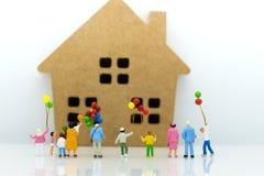 Miniaturleute: Kinder, die zu Hause Ballon mit Familie halten Bildgebrauch für internationalen Tag des Hintergrundes des Familien Lizenzfreie Stockfotografie