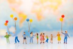 Miniaturleute: Kinder halten Ballone und Spiel zusammen, Hintergrund ist Karte der Welt Lizenzfreie Stockfotografie