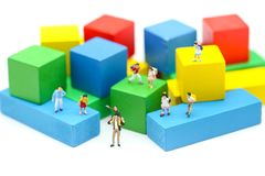 Miniaturleute: Kinder und Student mit Farbhölzernem Block Stockfoto