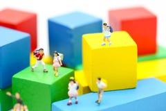 Miniaturleute: Kinder und Student mit Farbhölzernem Block Lizenzfreie Stockfotos