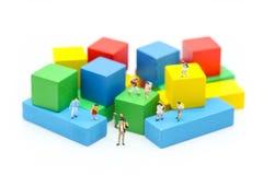 Miniaturleute: Kinder und Student mit Farbhölzernem Block Lizenzfreie Stockfotografie