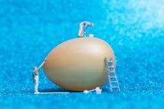 Miniaturleute: Maler malt Ostern-Eier für Ostern-Tag Stockbilder