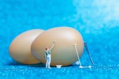 Miniaturleute: Maler malt Ostern-Eier für Ostern-Tag Stockfotografie