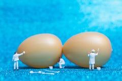 Miniaturleute: Maler malt Ostern-Eier für Ostern-Tag Lizenzfreie Stockfotos