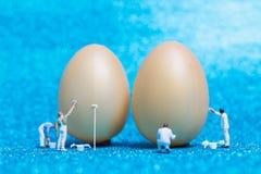 Miniaturleute: Maler malt Ostern-Eier für Ostern-Tag Lizenzfreies Stockbild