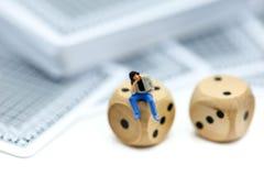 Miniaturleute: Mann, der auf Rolls sitzt, den ein hölzernes mit Münze würfelt Lizenzfreie Stockfotos