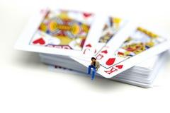 Miniaturleute: Mann, der auf Spielkarten sitzt Stockfotos