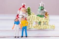 Miniaturleute: Mann- und Frauenzahlen, die auf dem Boden w stehen Stockfoto