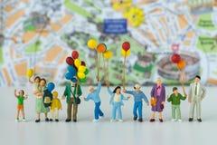 Miniaturleute mit der Familie, die Ballone mit Karte im Ba hält Stockfotografie