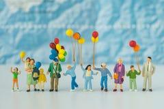 Miniaturleute mit der Familie, die Ballone mit blauer Karte in t hält Stockfotografie