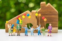 Miniaturleute mit der glücklichen Familie, die Ballone mit hölzernem hält Lizenzfreies Stockfoto