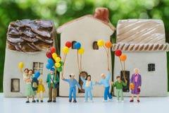 Miniaturleute mit der glücklichen Familie, die Ballone mit keramischem hält Stockbilder