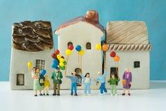 Miniaturleute mit der glücklichen Familie, die Ballone mit keramischem hält Stockfoto