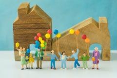 Miniaturleute mit der glücklichen Familie, die Ballone vor hält Lizenzfreie Stockfotos