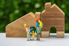 Miniaturleute mit der glücklichen Familie, die Ballone vor hält Stockbilder