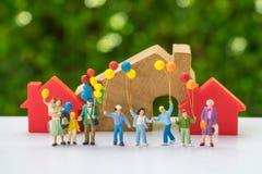 Miniaturleute mit der glücklichen Familie, die Ballone vor hält Lizenzfreies Stockfoto