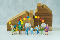Miniaturleute mit der glücklichen Familie, die Ballone vor hält Lizenzfreie Stockfotografie