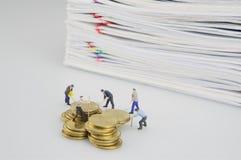 Miniaturleute mit Goldmünzen und Stapelüberlastungsdokument lizenzfreie stockbilder