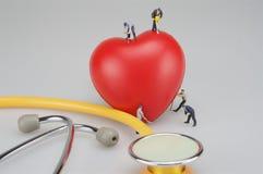 Miniaturleute mit rotem Herzen und Stethoskop lizenzfreie stockfotos