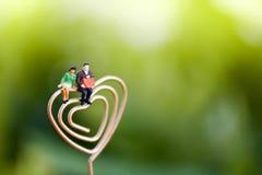 Miniaturleute-Paar-Liebhaber, der auf Herzen sitzt Zu küssen Mann und Frau ungefähr Lizenzfreie Stockbilder