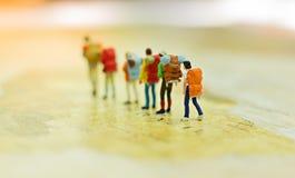 Miniaturleute, Reisende mit dem Rucksack, der auf der Weltkarte, gehend zum Bestimmungsort steht Stockbild