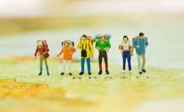 Miniaturleute, Reisende mit dem Rucksack, der auf der Weltkarte, gehend zum Bestimmungsort steht Stockfotos