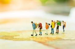 Miniaturleute, Reisende mit dem Rucksack, der auf der Weltkarte, gehend zum Bestimmungsort steht Stockfoto