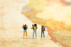Miniaturleute: Reisende mit dem Rucksack, der auf der Weltkarte, gehend zum Bestimmungsort steht Bildgebrauch für Reiseveranstalt Lizenzfreie Stockfotografie
