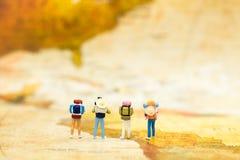 Miniaturleute: Reisende mit dem Rucksack, der auf der Weltkarte, gehend zum Bestimmungsort steht Bildgebrauch für Reiseveranstalt Lizenzfreies Stockbild