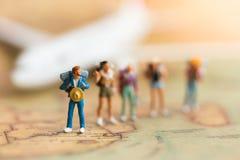 Miniaturleute: Reisende mit dem Rucksack, der auf Weltkarte steht Lizenzfreie Stockfotos