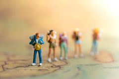 Miniaturleute: Reisende mit dem Rucksack, der auf Weltkarte steht, Stockfotografie
