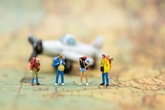 Miniaturleute: Reisende mit dem Rucksack, der auf Weltkarte steht, reisen mit dem Flugzeug Bildgebrauch für Reiseveranstalterkonz Lizenzfreie Stockfotografie