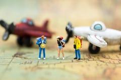 Miniaturleute: Reisende mit dem Rucksack, der auf Weltkarte steht, reisen mit dem Flugzeug Bildgebrauch für Reiseveranstalterkonz Lizenzfreie Stockfotos