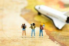 Miniaturleute: Reisende mit dem Rucksack, der auf Weltkarte steht, reisen mit dem Flugzeug Bildgebrauch für Reiseveranstalterkonz Stockfoto