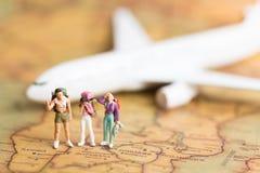 Miniaturleute: Reisende mit dem Rucksack, der auf Weltkarte steht, reisen mit dem Flugzeug verwendet als Reiseveranstalterkonzept Stockfotos