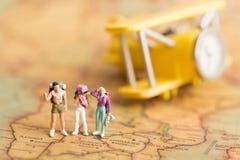 Miniaturleute: Reisende mit dem Rucksack, der auf Weltkarte steht, reisen mit dem Flugzeug verwendet als Reiseveranstalterkonzept Stockbild