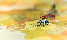 Miniaturleute, Reisende mit Fahrrad auf der Weltkarte, cyling zum Bestimmungsort Lizenzfreies Stockfoto