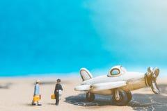 Miniaturleute: Reisende mit Flugzeug auf der Weltkarte Lizenzfreies Stockfoto