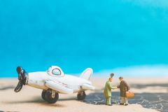 Miniaturleute: Reisende mit Flugzeug auf der Weltkarte Stockfotografie