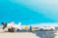 Miniaturleute: Reisende mit Flugzeug auf der Weltkarte Stockbilder