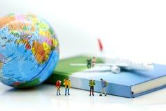 Miniaturleute: Reisende mit Weltkugel und Flugzeug, tra stockfoto