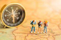 Miniaturleute: Reisende stehen auf der Kartenwelt und gehen zum Bestimmungsort Gebrauch als Dienstreisekonzept lizenzfreies stockbild