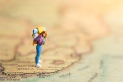 Miniaturleute: Reisender, der auf die Karte geht Verwendet, um zu den Reisezielen auf Reiseveranstalterhintergrundkonzept zu reis stockbilder