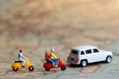 Miniaturleute: Reisender, der ein Motorrad auf Karte mit Auto reitet, Stockfotografie