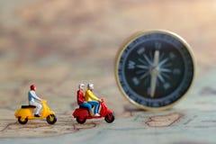 Miniaturleute: Reisender, der ein Motorrad auf Karte reitet Stockfotografie